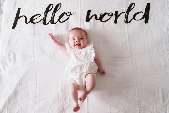 Happy cute baby girl lying on blanket under Hello World text at home