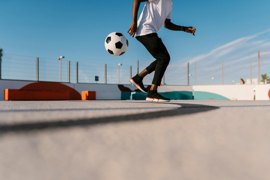 Young man juggling with soccer ball in sports court against sky
