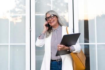 Happy senior female professional talking on smart phone while looking away against door