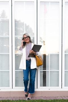 Smiling female entrepreneur talking on smart phone while holding file against office door