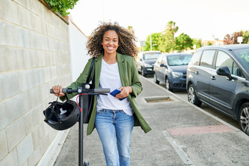 Happy young woman walking with electric push scooter on sidewalk in city
