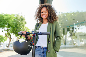 Happy young woman standing with electric push scooter on road
