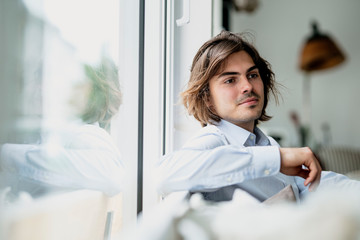 Close-up of confident male owner sitting against bookshelf in cafe