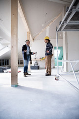 Male building contractors planning while standing in constructing house