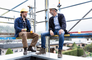 Male architects talking while sitting at construction site
