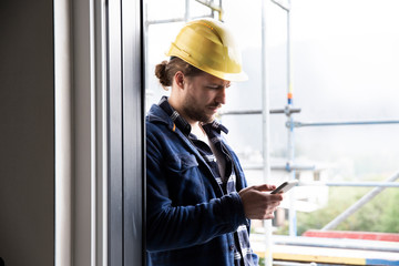 Male architect wearing helmet using smart phone by window at constructing house