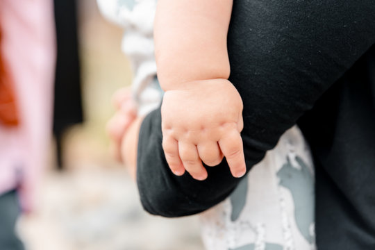 Chubby baby hand hanging over mom's shoulder