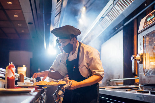 Chef wearing protective face mask preparing a dish in restaurant kitchen