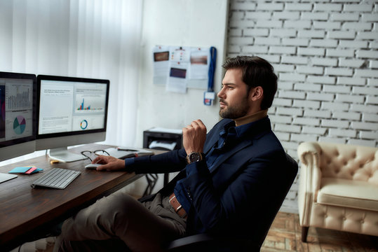 Side view of young successful businessman or sales manager analyzing financial data on computer, looking at statistics on pc screen while sitting at his workplace in the modern office