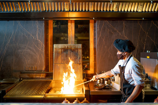 Chef wearing protective face mask preparing grill in restaurant kitchen
