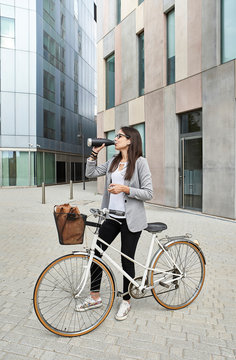 Businesswoman drinking water while standing with bicycle on city street