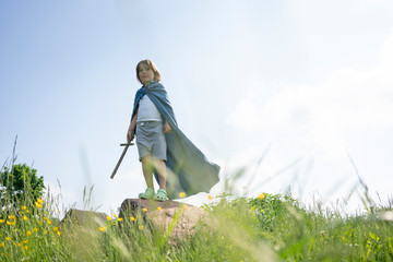 Playful boy wearing cape standing on rock against sky during sunny day
