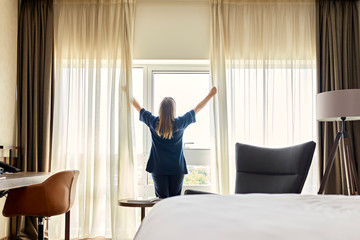 Chambermaid opening curtains of window in hotel room