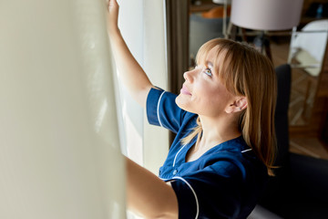 Close-up of chambermaid opening curtains of window in hotel room