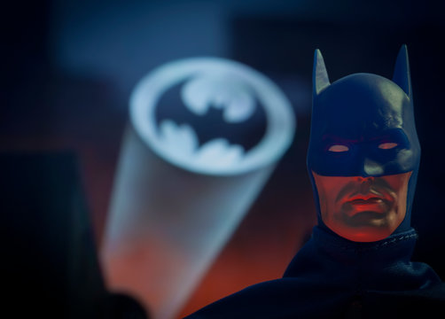NEW YORK USA, APRIL 15 2020: Portrait of crime fighter Batman with the bat signal over Gotham City - Mego Corp. action figure
