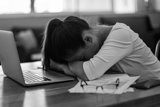 Tired woman stressed out from work, at her computer at home.