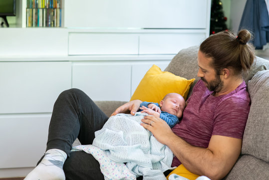 Smiling Caucasian man father sitting on sofa with holding his newborn baby son. Parent and cute infant child boy are relax together at home. Happy family and baby healthcare concept