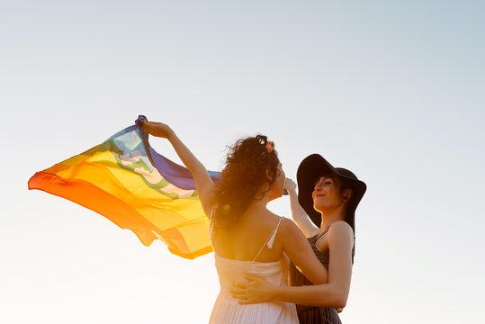 Happy women raising multicolored flag standing on sea beach