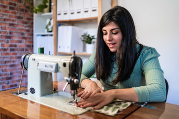 Craftswoman using modern sewing machine while creating soft fabric samples with creative green pattern near lamp in loft style workshop
