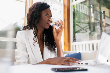 Low angle of black confident woman drinking water from glass while using netbook during work in cozy workplace in cafe