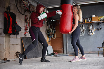 Sportswomen punching bag during boxing training