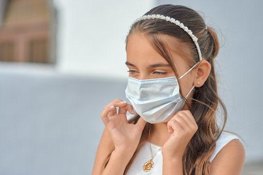 Preteen blond girl in a white dress wearing a protective mask because of the covid-19 pandemic, on the day of her first communion standing outside a church