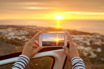 Back view of unrecognizable female tourist standing near car and taking photo of amazing sunset over ocean on mobile phone