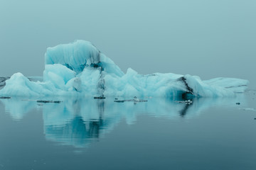 Magnificent view of big icebergs surrounded by silent sea with ripples on surface in overcast weather in winter in Iceland Fotobehang