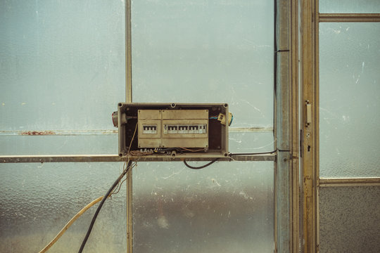 Broken control panel of circuit breaker placed on glass wall of abandoned building