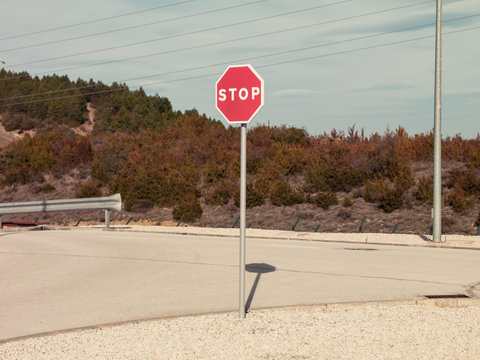Round red prohibitory road sign with word stop on empty asphalt roadway in dry rural terrain