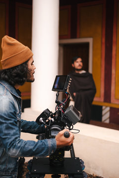 Side view faceless male video operator in casual denim jacket and hat shooting video of actor on modern professional camera