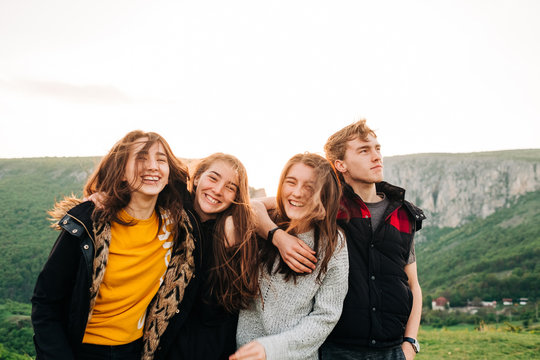 Group of happy friends hugging together on background of spectacular mountainous landscape in Transylvania and cheerfully looking at camera during vacation