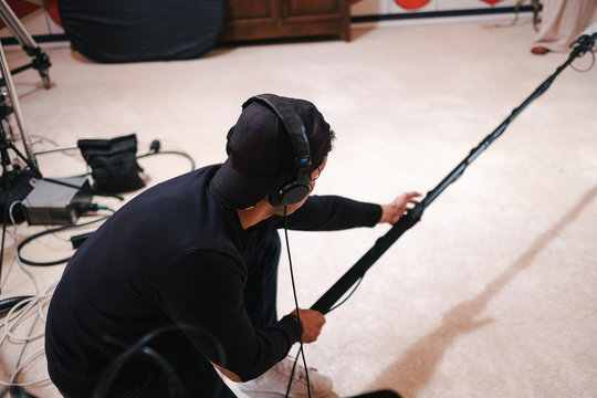 Back view faceless assistant crouched using professional shotgun microphone while working in creative studio during video recording