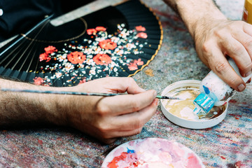 From above crop anonymous male artist pouring white gouache into palette while drawing floral pattern on hand fan in workshop