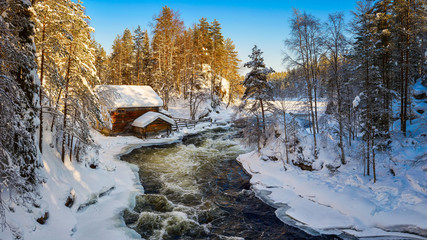 Small cozy wooden house located in picturesque forest covered by snow near wild river against cloudless blue sky