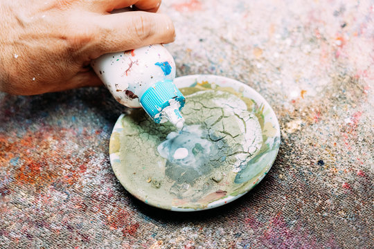 From above crop unrecognizable male artist pouring white paint into weathered palette while working in workshop