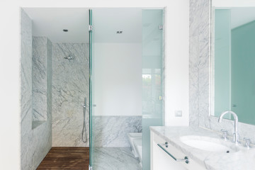Creative design of clean bathroom with marble walls and oval sink under stainless steel tap near shower room with glass door close to bidet and toilet bowl