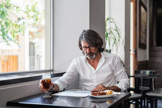 Positive ethnic bearded aged man sitting at table with of glass of foamy beer and reading newspaper near window