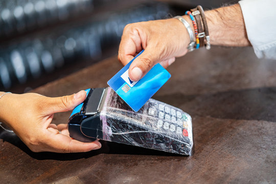 Cropped unrecognizable person standing at counter helping client to pay using POS machine and credit card working in cafe