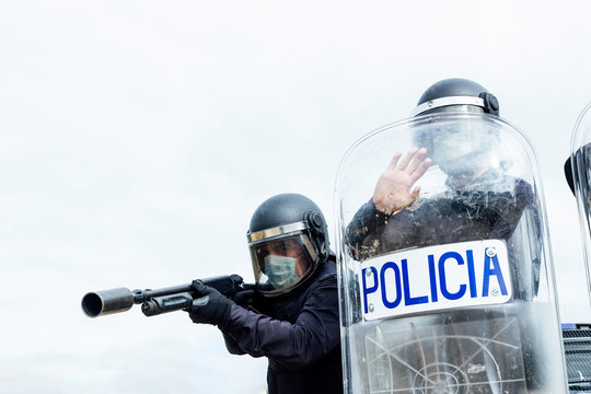 Low angle of swat soldiers in protective uniforms and medical masks armed with assault rifle and riot shield and ready for fight