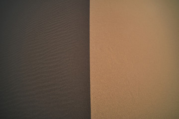 From above of abstract background of light brown sand with smooth dry surface near dark brown rippled terrain with loose texture in desert