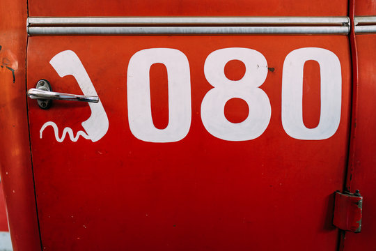 Closeup of bright red fire truck door with metal handle and dense structure with number for calling in emergency
