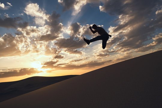 Silhouette of anonymous fit male dancer performing trick with reached leg above sandy terrain in desert at bright sundown at night
