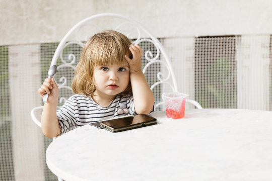 Cute little girl sitting at table in backyard and watching cartoon while enjoying delicious jelly dessert in summer looking at camera