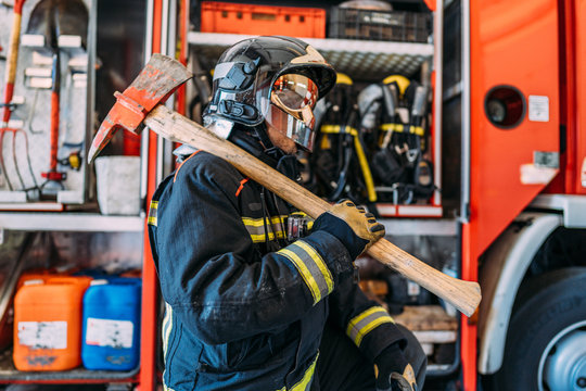 Side view of unrecognizable firefighter in uniform and hardhat carrying big used pickax with wooden handle while standing near fire truck with professional tools and safety vests