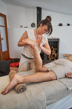 Female therapist standing near massage table and stretching leg of male patient