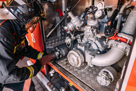 From above side view of crop anonymous fireman in protective helmet and uniform using hose and fire pump with stainless steel tubes under measuring devices installed in fire truck