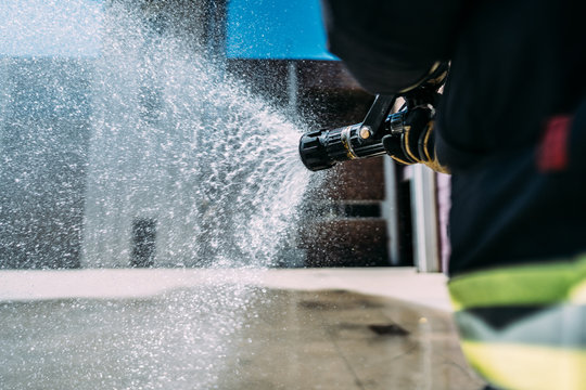 Side view of anonymous fireman in uniform and protective helmet using hose with plastic edge splattering pure water near garage with fire trucks
