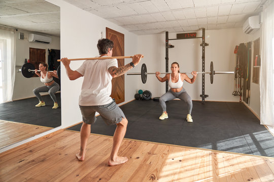 Full body of woman training with personal male instructor and doing squat with barbell in contemporary sport center