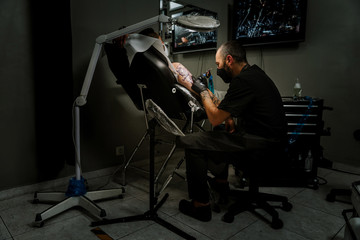 Side view of male with face mask master tattooing unrecognizable client lying in chair near floor lamp in tattoo parlor while using tattoo machine